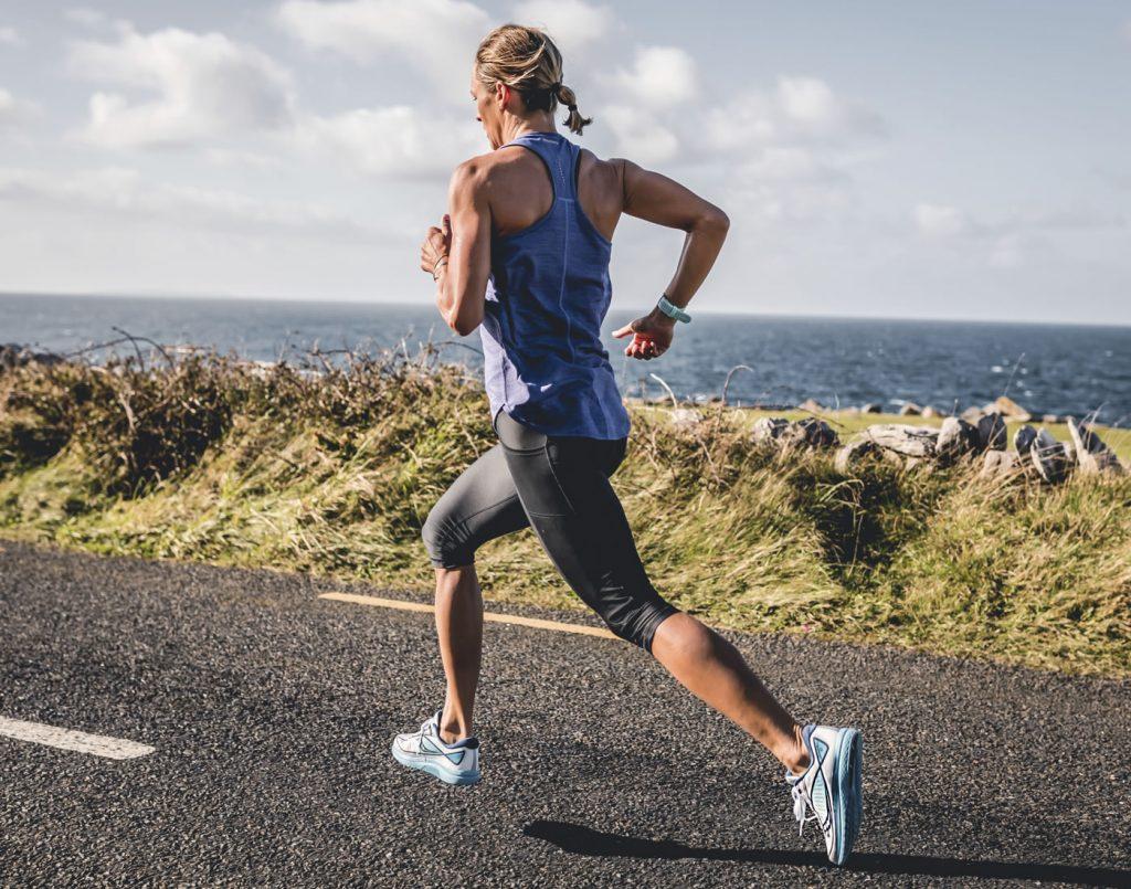 Läuferin auf einer Straße beim Training mit 3/4 leggins und run singlet
