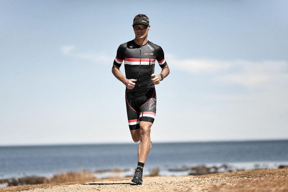 Alexander im 2XU Triathloneinteiler am Strand laufend