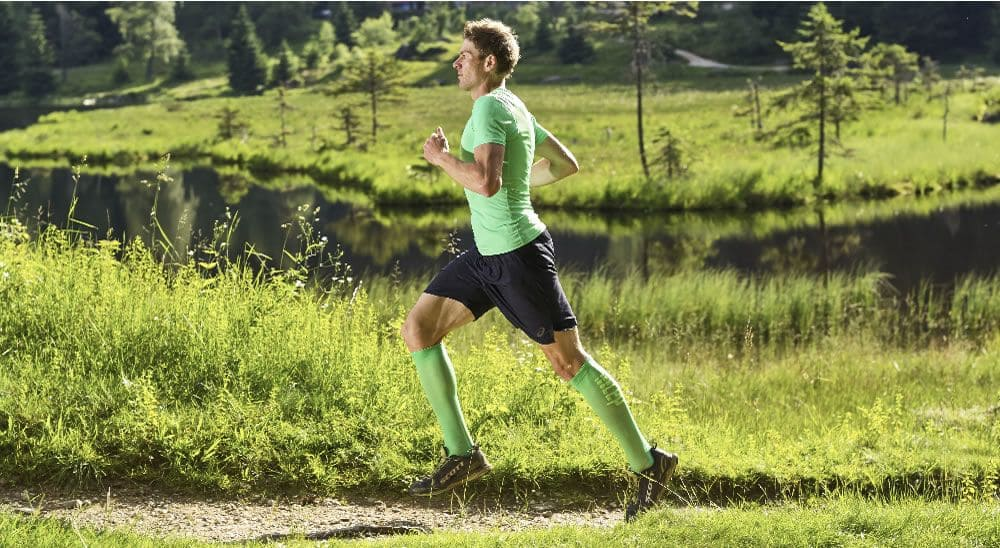 Läufer in der Natur der von CEP Kompressionssocken und Shorts und T-shirt trägt